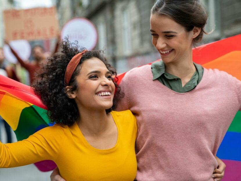 ragazze che si abbracciano sotto la bandiera del gay pride, uso della schwa